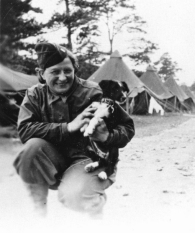 Female in Army uniform kneels down to play wiht a little dog.