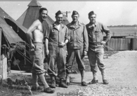 Four men standing next to tents.