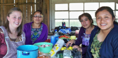 Mona Almobayyed sits at a table with three local women in Guatemala.