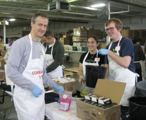 At Matthew 25 Ministries, UC Peace Corps volunteers process soap to send abroad. From the left are Jamey Pratt, Lauryn Alleva and Dan Rankin. (Wendell Mettey, A&S '68, is founder and president of M25M.)