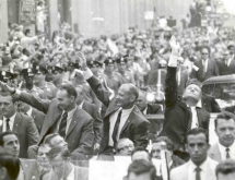 Apollo crew sitting in a car during a giant ticker-tape parade in New York City.