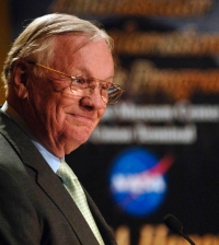 Head shot of Neil Armstrong with NASA logo in the background