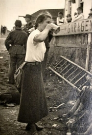 A woman getting a drink in the battle field.