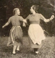Two young women do a folk dance.