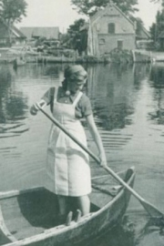 A young woman rowing a boat on a pond.