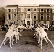 An exercise throwing balls. The women are wearing white dress-like uniforms.