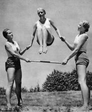 One girl jumping over a pole, held by two other girls.
