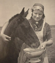 A young woman pets a horse while feeding it.