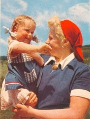 Young woman holds a pig-tailed toddler.