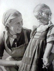 A German girl in the program helps a young girl read.