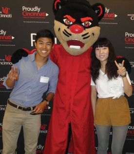 Two international students stand with the Bearcat, who is wearing a graduation gown