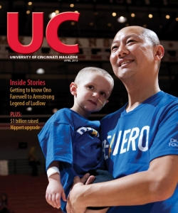 Santa Ono holds a child with cancer on the cover of UC Magazine