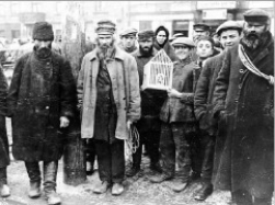Jewish men standing in a filthy ghetto
