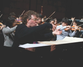 Randy Edelman conducting students from the piano