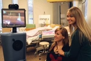 A UC nursing student holds a stethescope on the heart of another student to show how Flos demonstrate how Flo the robot can record a heartbeat.