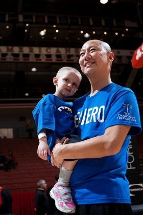 UC President Santa Ono holds Katie, a young cancer patient, soon after having his head shaved in front of thousands at UC's Fifth Third Arena in January 2013 to help raise funds for the Dragonfly Foundation. photo/Ashley Kempher