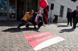 Santa Ono and a UC student points to a ground cling on campus that helped announce his selection as president.