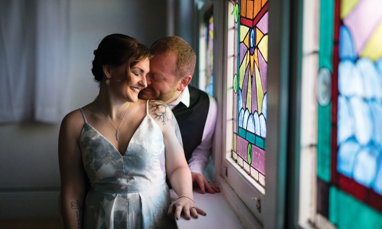 Tori Thomas and her husband Nelson pose in front of a stained glass window.