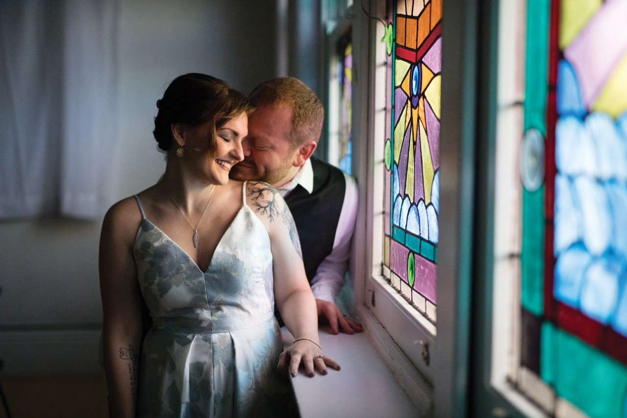 Husband and wife pose near stained glass window