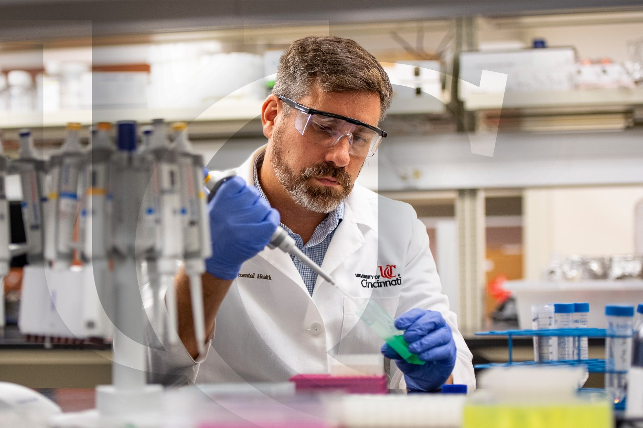 Principal investigator Scott Langevin fills a vile in a research lab