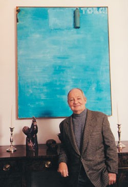 "UC alumnus Douglas Cramer poses in his dining room before ""Blue,"" an abstract by Cincinnati's Jim Dine, one of Cramer's closest friends and one of his favorite contemporary artists. photo/Philip Greenberg"