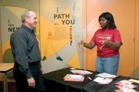 """Tom Vick, DAAP '69, of Chicago, engages with UC sophomore and Office of Admissions student ambassador Jennifer Moore in college-fair role-playing at a recent UCART training session. """"We tell the students, 'Come and see the campus. You'll be surprised,"""" Vick says."""