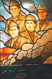 Stained glass window depicts head shots of each of the four chaplains.