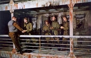Four chaplains standing next to the railing of the ship, helping a soldier overboard.
