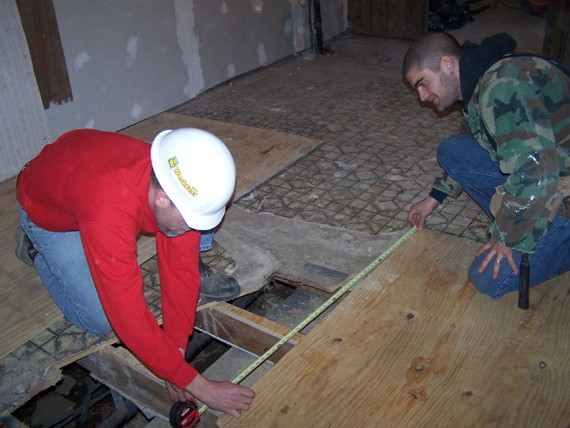 Replacing sagging floorboards with stronger, safer flooring is one way volunteers led by UC alumnus Bryan Byrd, CAS '89, (in red shirt) are helping poor and elderly residents of eastern Kentucky.