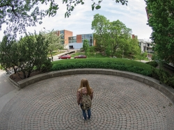 A female student stands with her back to the camera in the center of Echo Point , a circular brick paver structure behind Braustein Hall.