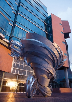 This outdoor sculpture is aluminum ribbons wrapped around each other to make a tornado shape.