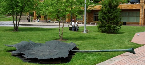 A very large bronze leave lays in the lawn as if blown off a tree