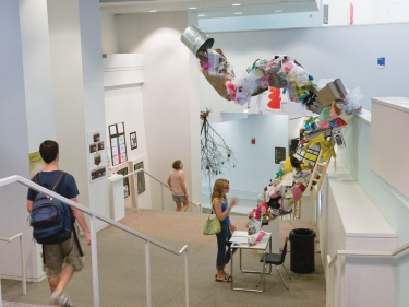 """A crazy sculpture in the halls of DAAP has a """"floating"""" garbage can overturned and colorful papers falling out."""