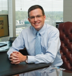 Jay Hummel, wearing a blue shirt and tie, sits at a desk with hands folded looking into the camera.