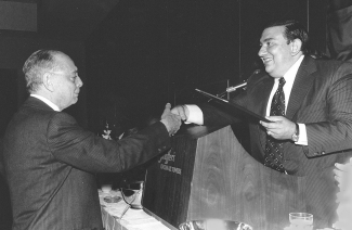 Former UCAA Director Chris Demake shakes a man's hand at a podium during a UC event.