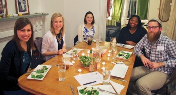 Five University of Cincinnati alumni pose around a dinner table.