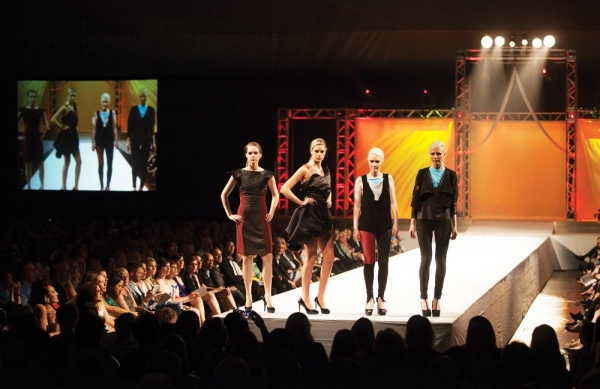 Four models pose at the end of the runway of the DAAP annual spring fashion show.