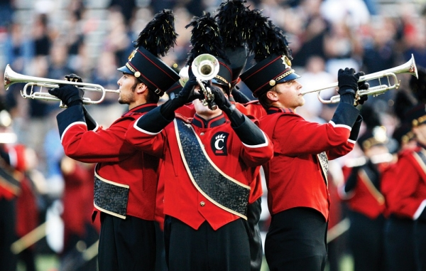 Three trumpet players put their backs together to create of cone of sound. They are members of the University of Cincinnati Marching Band.