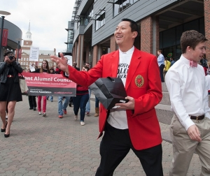 President Ono marches in parade and tosses out goodies from a black bag.