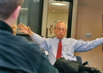 Jim Kautz, seated at his desk in shirt and tie, motions with both arms.