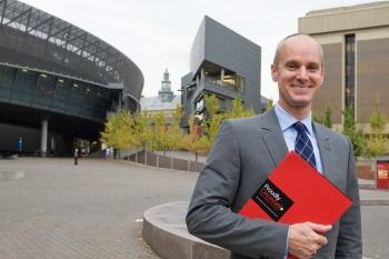 UC Alumnus Drew Becher stands on campus holding a red Proudly Cincinnati folder.
