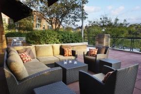 A sofa in an obvious outdoor patio. Restaurant patios overlook University Commons at the University of Cincinnati Kingsgate Marriott.