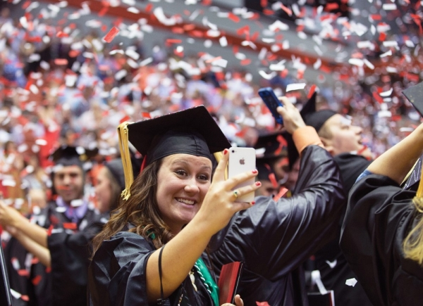 A UC graduate in black cap and gown takes a selfie with her cell phone while confetti falls on the crowd behind her.