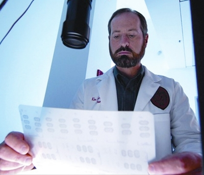 UC researcher Kim Seroogy examines results in his lab.