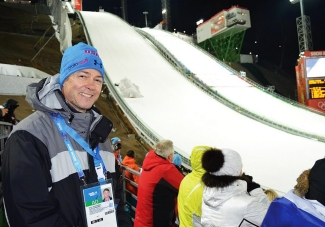 Grant Schaffner stands in front of a competition sledding track at the Sochi Olympics