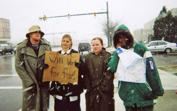 "Four members of UC's homelessness experience stand in the snow with a ""will work for food sign."""
