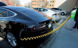 A black car is plugged in and charging at the unveiling of UC's first electric vehicle charging station near Wherry Hall on the medical campus. Additional stations are planned for West Campus.