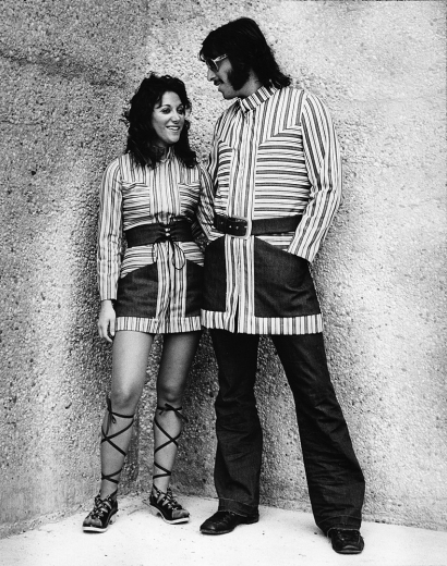 A male and female student from the 1970s stand near Crosley Tower posing in pin-striped threads likely as part of the DAAP Fashion Show.