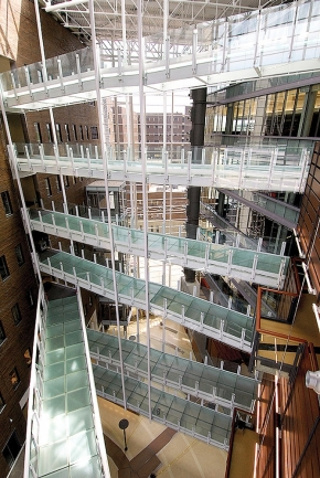 "A dramatic overview of a set of ""bridges"" on many floors inside the UC CARE/Crawley building."
