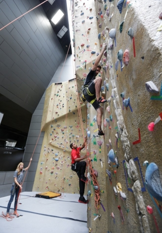 A couple of guys try their hands (and feet) on the 40-foot climbing wall at the University of Cincinnati's Campus Recreation Center